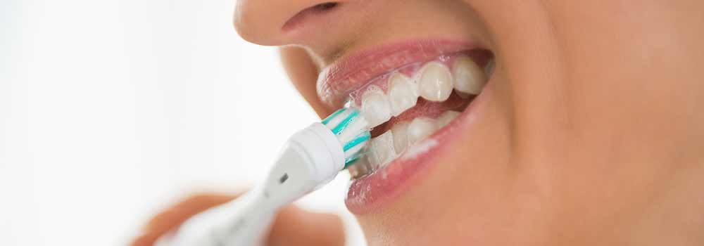 Womans Teeth Being Brushed With Electric Toothbrush