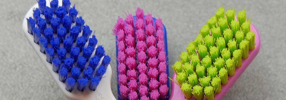 Close up of three colourful toothbrush heads