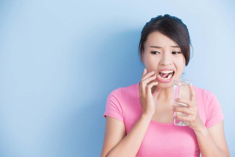 Woman with sensitive teeth and a glass of water