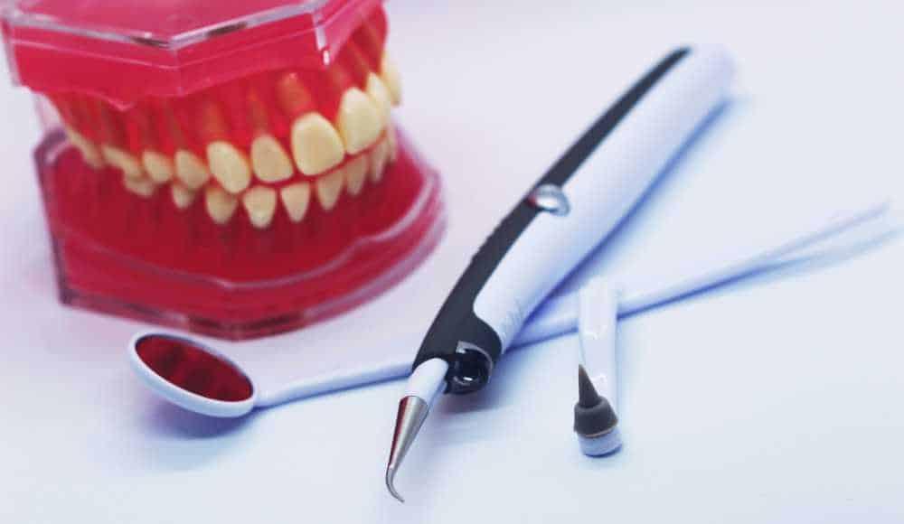 Dental tools and plaque scraper next to model of teeth