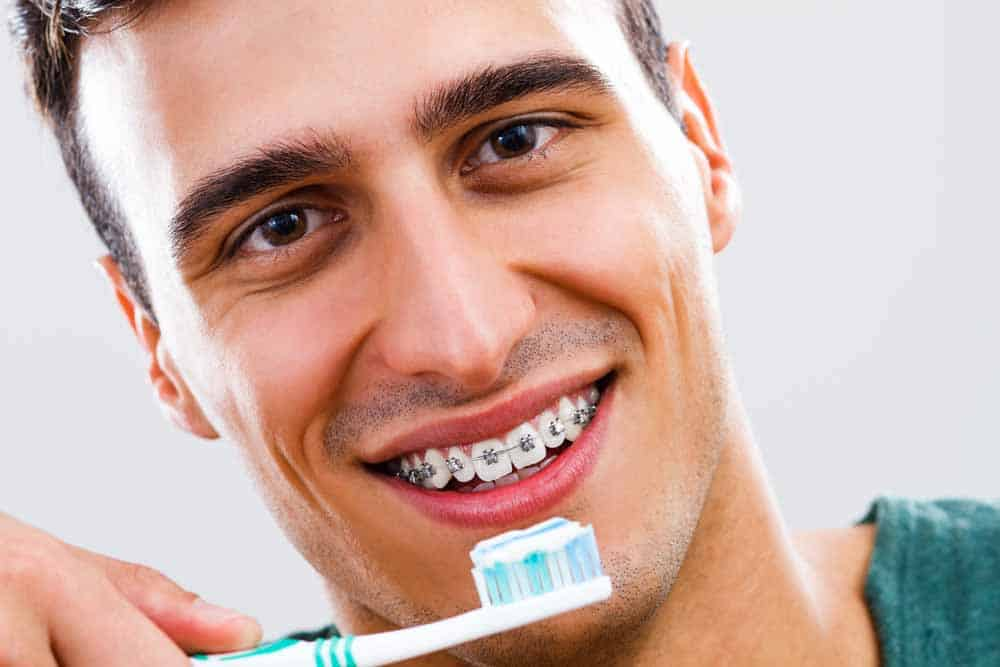 Man holding toothbrush with toothpaste in front of teeth fitted with braces