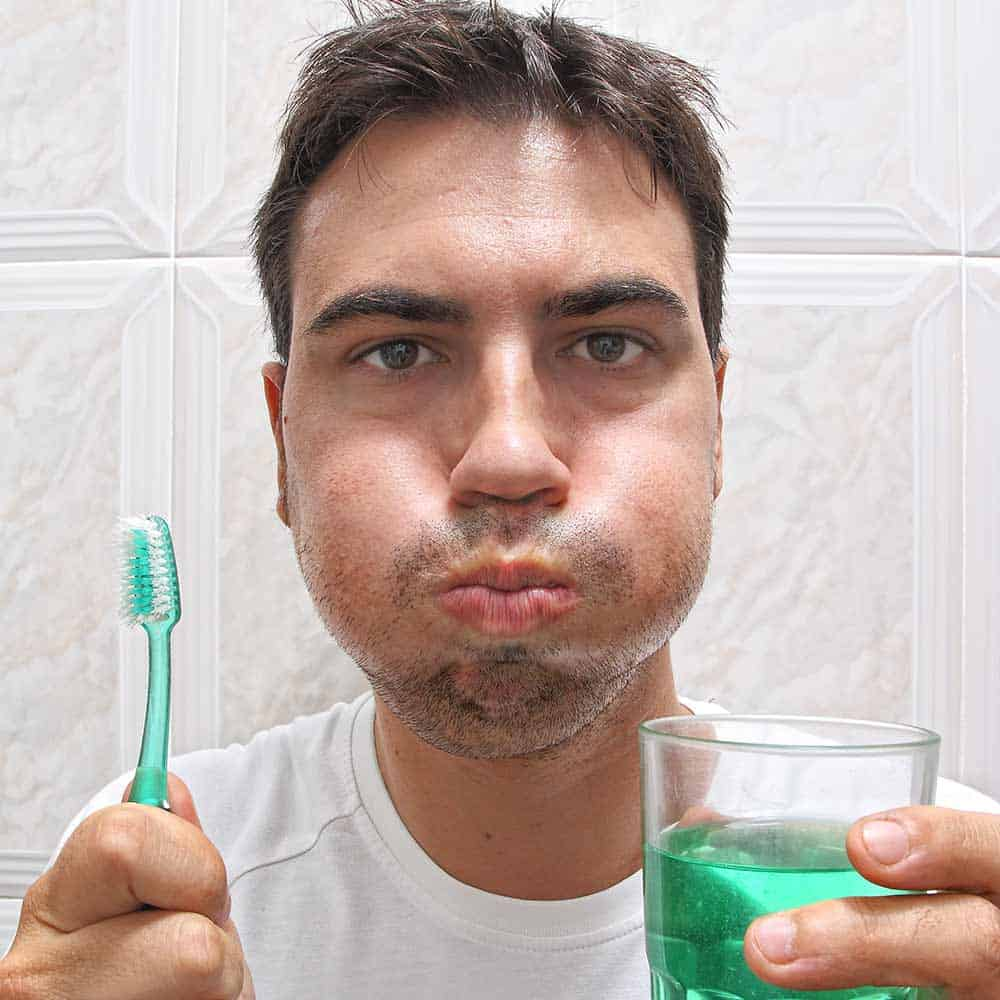 Man holding glass of mouthwash whilst rinsing