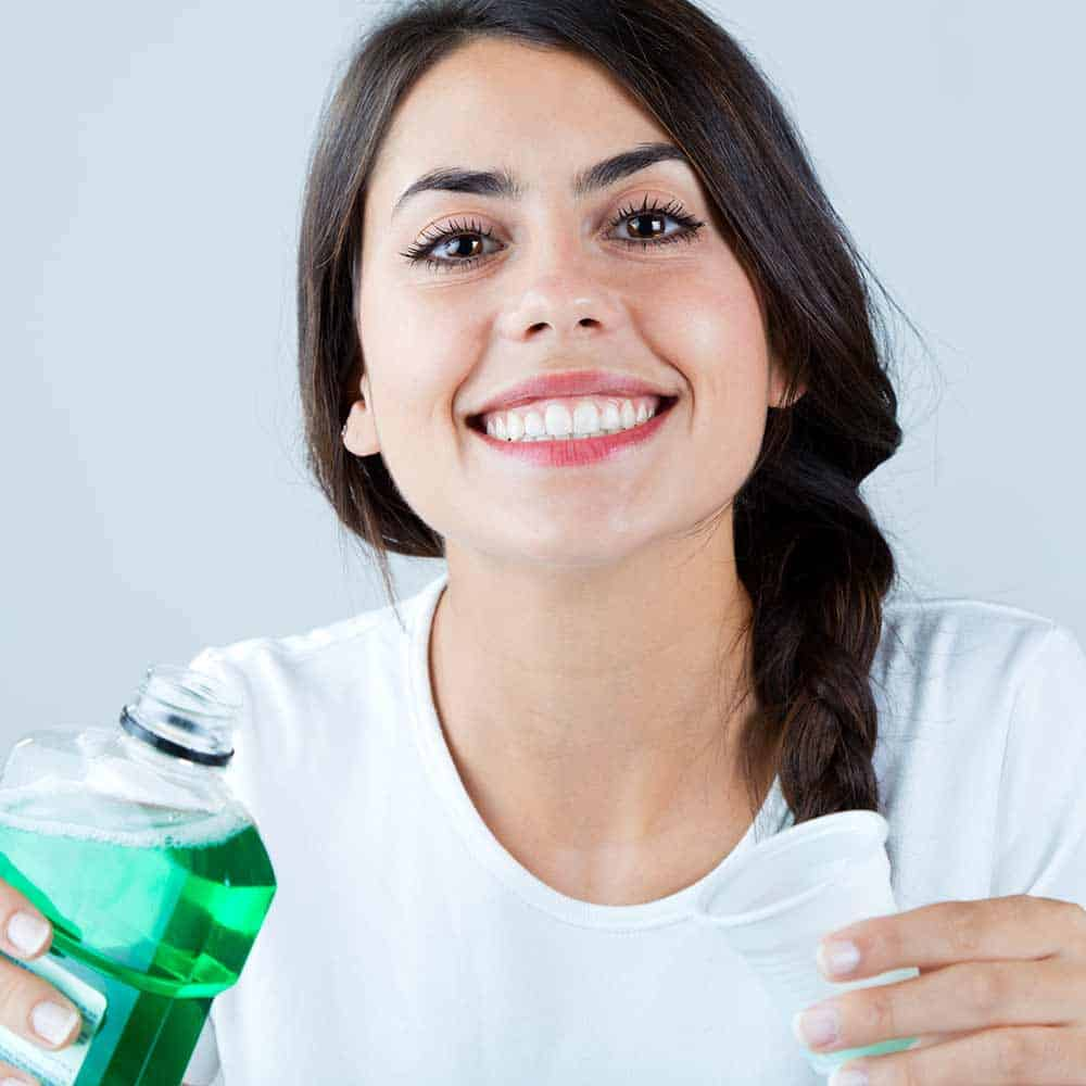 Woman holding bottle of open mouthwash